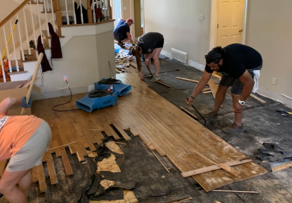 <strong>Germantown residents help rip up hardwood flooring ruined by water at Ladi Nyenwe&rsquo;s house after flooding in June 2019.</strong> (Submitted)