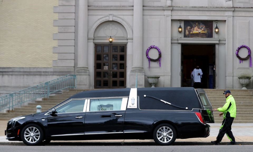 <strong>A funeral home employee opens the door of a hearse at Immaculate Conception Cathedral in Midtown on March 23, 2021.</strong> (Daily Memphian file)