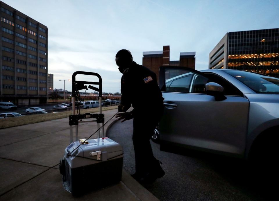 <strong>Firefighter Muhammad Babandi loads a portable cold storage unit containing Pfizer's COVID-19 vaccine outside Regional One Health just before dawn March 16, 2021. (Patrick Lantrip/Daily Memphian)</strong>