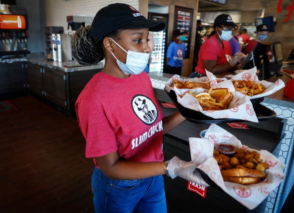<strong>Server Lovie Pope delivers food to customers at the new Slim Chickens restaurant on Friday, March 26, in Collierville.</strong> (Mark Weber/The Daily Memphian)