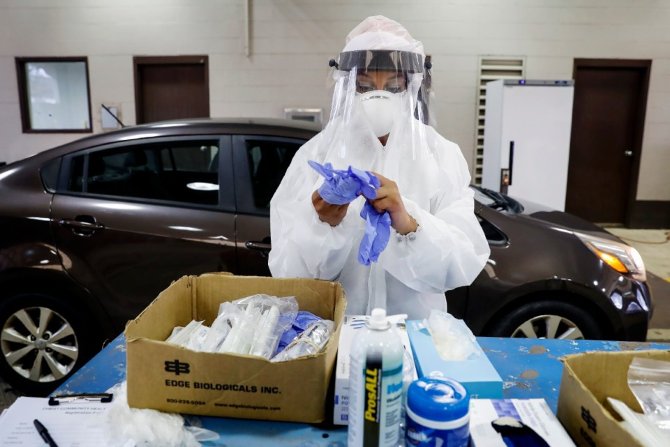 <strong>A Christ Community Health Services staff member collects nasal swabs at a drive-thru coronavirus testing site.</strong> (Mark Weber/The Daily Memphian file)