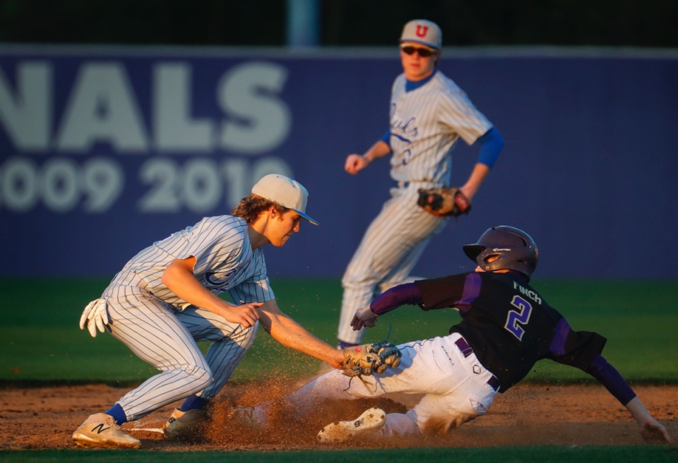 <strong>CBHS runner Ethan Finch (right) slides safely past the tag of MUS shortstop Ben Burkhart (left) on Monday, March 29.</strong> (Mark Weber/The Daily Memphian)