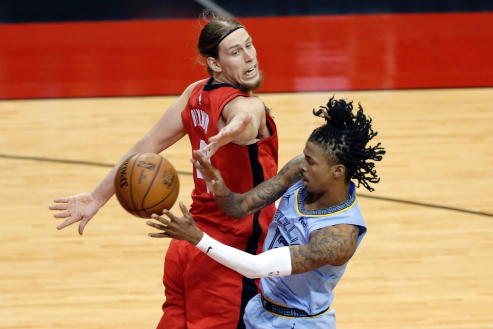 <strong>Grizzlies guard Ja Morant, right, passes the ball behind a surprised Houston Rockets forward Kelly Olynyk, left, on Monday, March 29, in Houston.</strong> (Michael Wyke/AP)
