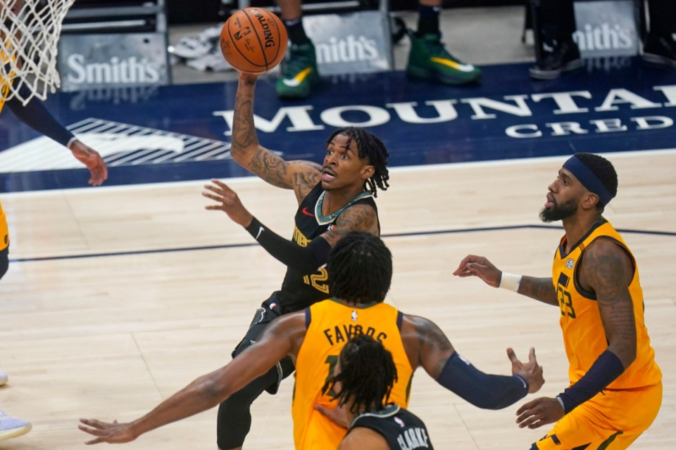 <strong>Grizzlies guard Ja Morant, rear, goes to the basket against the Utah Jazz on March 27. Utah was scheduled to play Memphis Wednesday, March 31, before the team&rsquo;s charter jet had to turn back Tuesday.</strong> (Rick Bowmer/AP file)