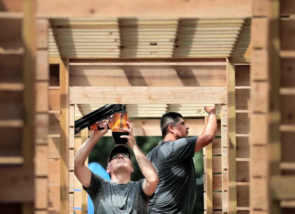 <strong>Volunteer architects Barry Allmon (left) and Oscar Andrade work on an outdoor classroom at the Carpenter Street Art Garden on Sept. 8, 2018. The art garden, a haven for kids in Binghamton from crime and violence in the neighborhood, is expanding with the opening of a tutoring house for the kids who go to the neighborhood refuge.</strong> (Jim Weber/Daily Memphian)