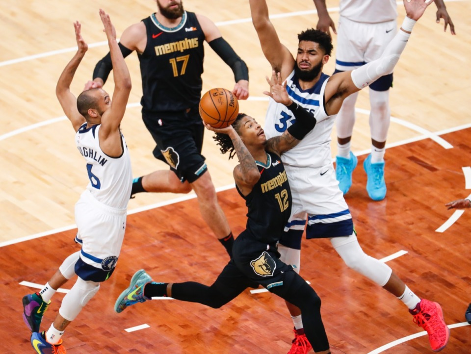 <strong>Grizzlies guard Ja Morant (middle) drives against Minnesota&rsquo;s Karl-Anthony Towns (right) on Friday, April 2, 2021.</strong> (Mark Weber/The Daily Memphian)