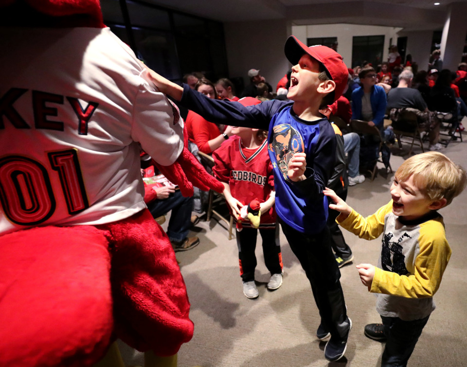 <strong>Whitman Steen (center), 8, and Carter Andrew McMinn (right), 6, charge gleefully toward Rockey the Redbird as the mascot greets fans at the Cardinals Caravan event Friday, Jan. 18, 2019. The annual event was held at AutoZone Park, where St. Louis Cardinals players and first base manager Stubby Clapp spoke with fans and signed autographs.</strong> (Houston Cofield/Daily Memphian)