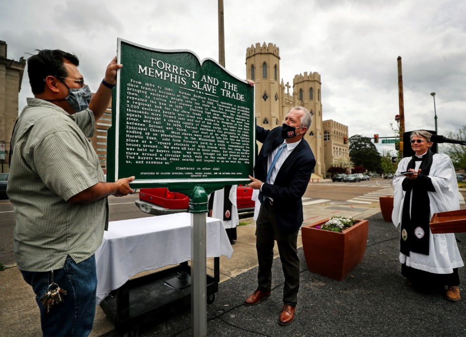 <strong>Helario Reyna (left) and Tim Huebner raise a rededicated plaque outside&nbsp; Calvary Episcopal Church in Downtown Memphis on Wednesday, April 7. The two-year-old historical marker noting the location of the Downtown slave market owned by Nathan Bedford Forrest was snapped off at its base and broken during the night on July 18, 2020.</strong> (Patrick Lantrip/Daily Memphian)