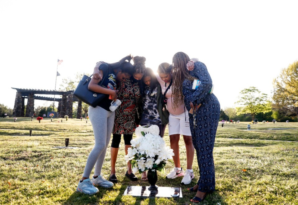 <strong>Shalanda Snearley (right) and family members pray over the grave of her son on April 5 at Memorial Park South Woods Cemetery. Her son, Korey Dupree, 26, was killed last year in a shooting at his Cordova-area apartment. She has filed a wrongful-death lawsuit against the apartment owners.</strong> (Mark Weber/Daily Memphian)