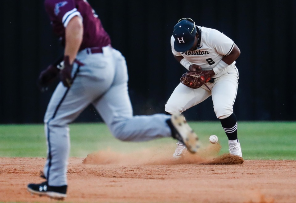 <strong>Houston second baseman Robinson Martin (right) drops a ground ball in the game against Collierville on April 8.</strong> (Mark Weber/The Daily Memphian)