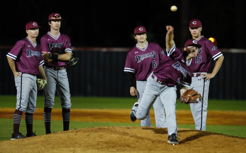 <strong>Collierville infielders watch as relief pitcher Ryan Neilson (front) warms up in the game against Houston on April 8.</strong> (Mark Weber/The Daily Memphian)