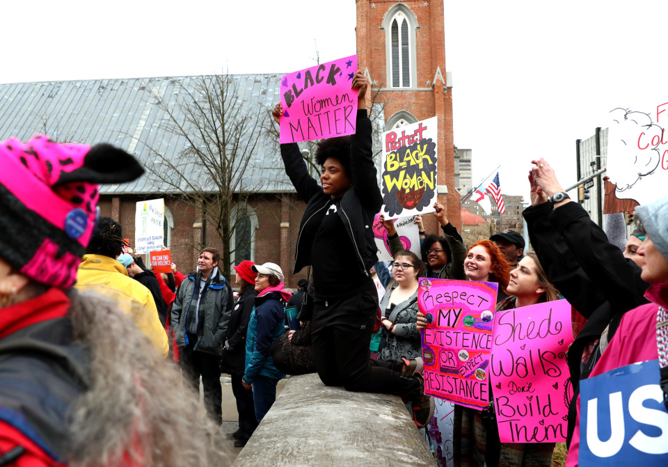 <strong>Kierra Batemon (center), 22, kneels on the steps of the courthouse in Downtown Memphis with around 200 other protesters that took part in the 2019 women's march. While the primary message of the march advocated equality for all women, many protesters spoke up about LGBTQ rights and President Donald Trump's efforts to build a border wall.</strong> (Houston Cofield/Daily Memphian)