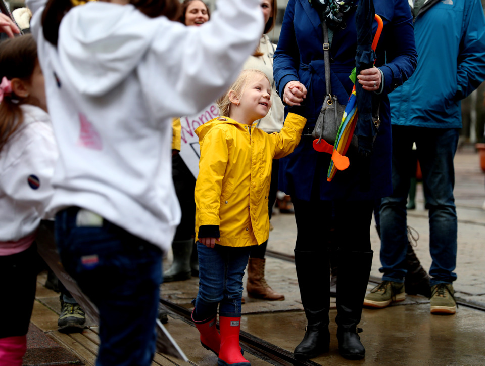 <strong>Attending her second women's march, Eleanor McMullen (center), 4, grasps her mother's hand as they make their way down Main Street. The march began at City Hall and ended at the courthouse in Downtown Memphis.</strong> (Houston Cofield/Daily Memphian)