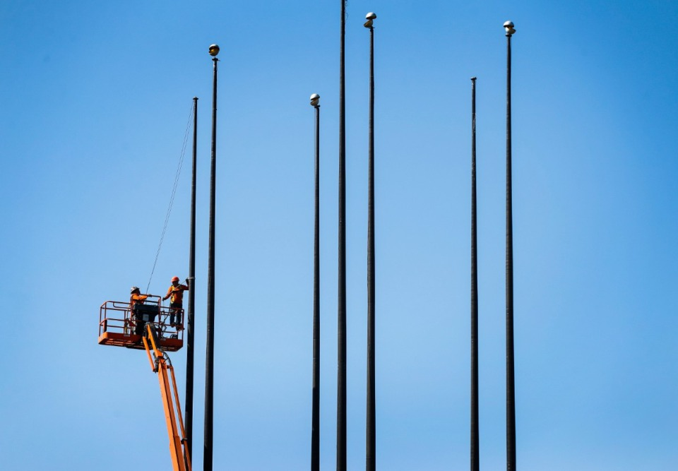 <strong>Workers with 901Demo.com begin the process of removing the seven flag poles from the south end of Mud Island on Tuesday, April 6.</strong> (Mark Weber/ Daily Memphian)