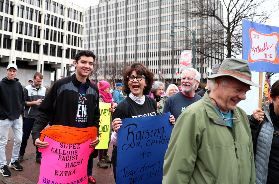 <strong>Marisa Soto Phipps (center) and her husband, Sean Phipps (right), laugh at some of the signage at the 2019 women's march. The march began at City Hall and ended at the courthouse in Downtown Memphis.</strong> (Houston Cofield/Daily Memphian)