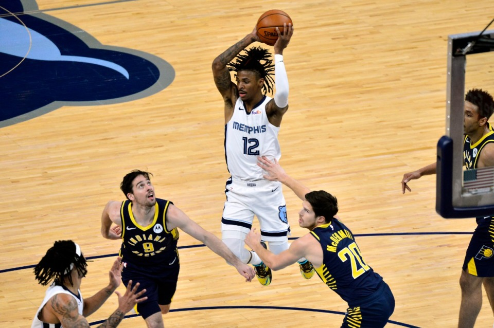 <strong>Memphis Grizzlies guard Ja Morant (12) handles the ball between Indiana Pacers guard T.J. McConnell (9) and forward Doug McDermott (20) in an NBA basketball game Sunday, April 11, 2021, at FedExForum.</strong> (Brandon Dill/AP)