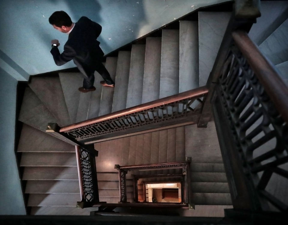 <strong>Jeff Higdon walks down a vertiginous stairwell in the Masonic Lodge on Court Avenue. The building, still home to active lodges, is full of history with architectural details, artifacts and symbols of a faded era.&nbsp;</strong>(Jim Weber/Daily Memphian file)