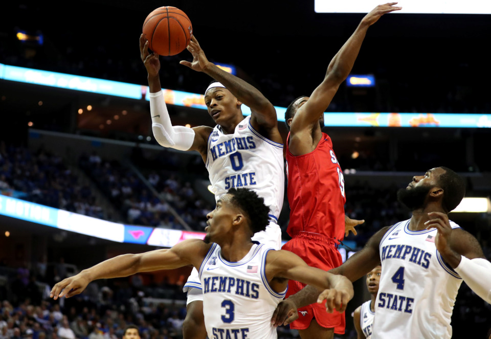 <strong>University of Memphis forward Kyvon Davenport (0) leaps over teammates and a Southern Methodist University defender for a rebound during a game against the Mustangs on Saturday, Jan. 19, 2019.</strong> (Houston Cofield/Daily Memphian)