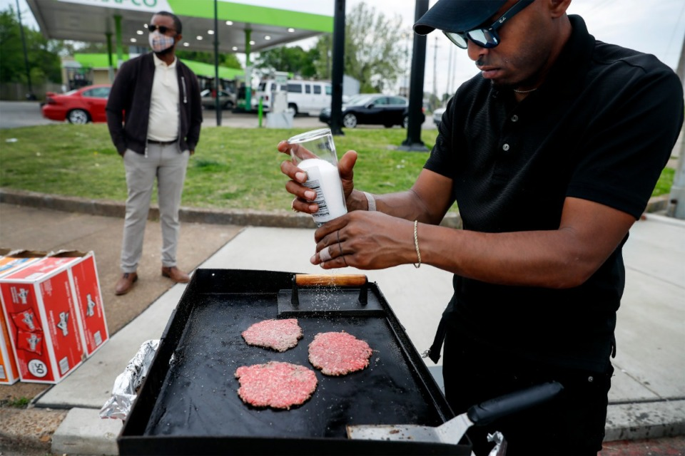 <strong>Aaron Branch, owner of A.D.&rsquo;s food cart, seasons his smash burgers on April 13 in front of the MAPCO station at Danny Thomas and MLK.</strong> (Mark Weber/The Daily Memphian)