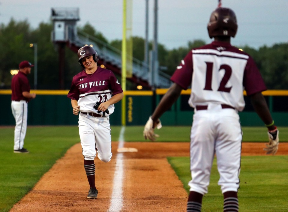 <strong>Collierville outfielder Marcus Lee (12) congratulates fellow outfielder Griffith Baird (22) as he makes his way home during the April 13 game against Arlington.</strong> (Patrick Lantrip/Daily Memphian)