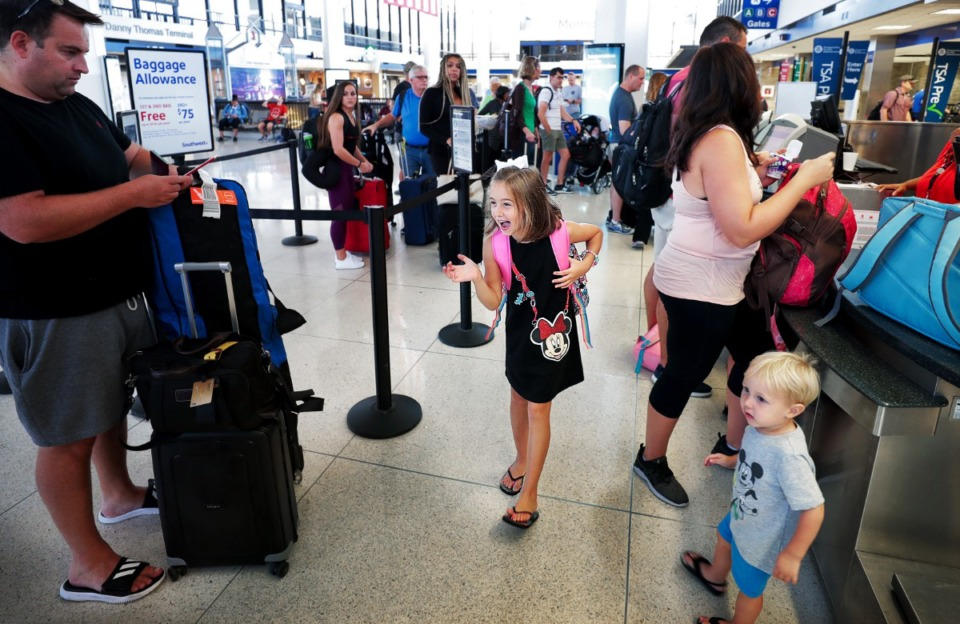 <strong>Excited members of the Trembly family get their boarding passes for a trip to Disney World in 2018.</strong> (Jim Weber/Daily Memphian file)