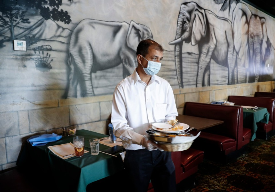 <strong>India Palace owner Bineder Kumar cleared a table during lunch time last June.</strong> (Mark Weber/Daily Memphian file)