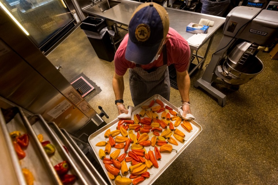 <strong>Lawerence Russell preps oven-smoked peppers and roasted garlic for Black Sheep&rsquo;s hot sauce. Russell rents commercial kitchen space at Church Health in Crosstown Concourse, where he makes one or two eight-gallon batches of hot sauce a week.</strong> (Ziggy Mack/Special to the Daily Memphian)