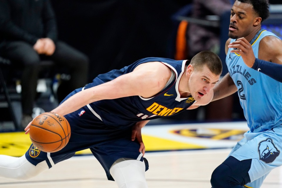 <strong>Denver Nuggets center Nikola Jokic, left, drives past Memphis Grizzlies center Xavier Tillman Sr. in the second overtime on April 19 in Denver. &nbsp;Jokic shot the go-ahead 3-pointer along with 44 other points, 15 rebounds and eight assists.</strong> (David Zalubowski/AP file)