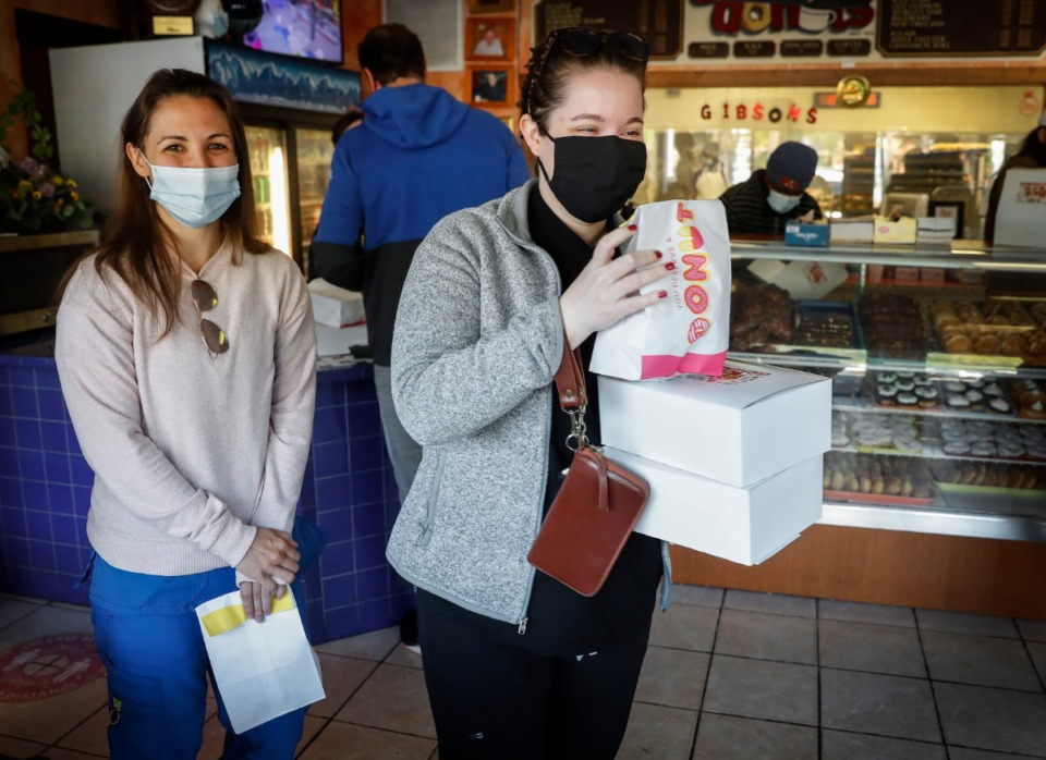 <strong>Gibson&rsquo;s Donuts customers Taylor Vracar (left) and Kaitlyn Polk (right) leave with free doughnuts on April 21 after The Kindness Revolution picked up their tab and in return asked them to perform an act of kindness.</strong> (Mark Weber/The Daily Memphian)