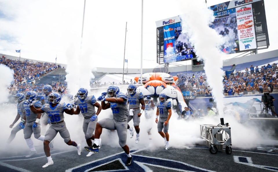 <strong>Pre-COVID, the Memphis Tigers head onto the field against Ole Miss at the Liberty Bowl Memorial Stadium on Aug. 31, 2019. With the easing of restrictions on outdoor activities, Dr. Stephen Threlkeld, infectious disease physician at Baptist Memorial Hospital-Memphis, said he expects football stadiums will safely reopen this fall.</strong> (Mark Weber/Daily Memphian file)