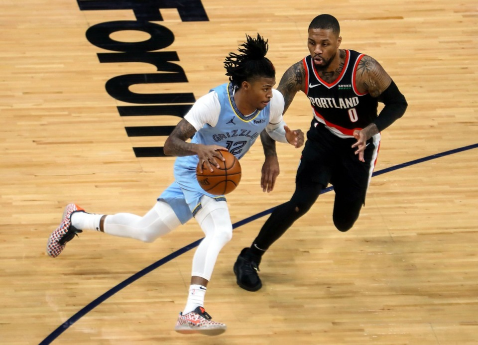 <strong>Grizzlies guard Ja Morant (12) drives against Portland Trail Blazers guard Damian Lillard (0) during the April 28 game at FedExForum.</strong> (Patrick Lantrip/Daily Memphian)