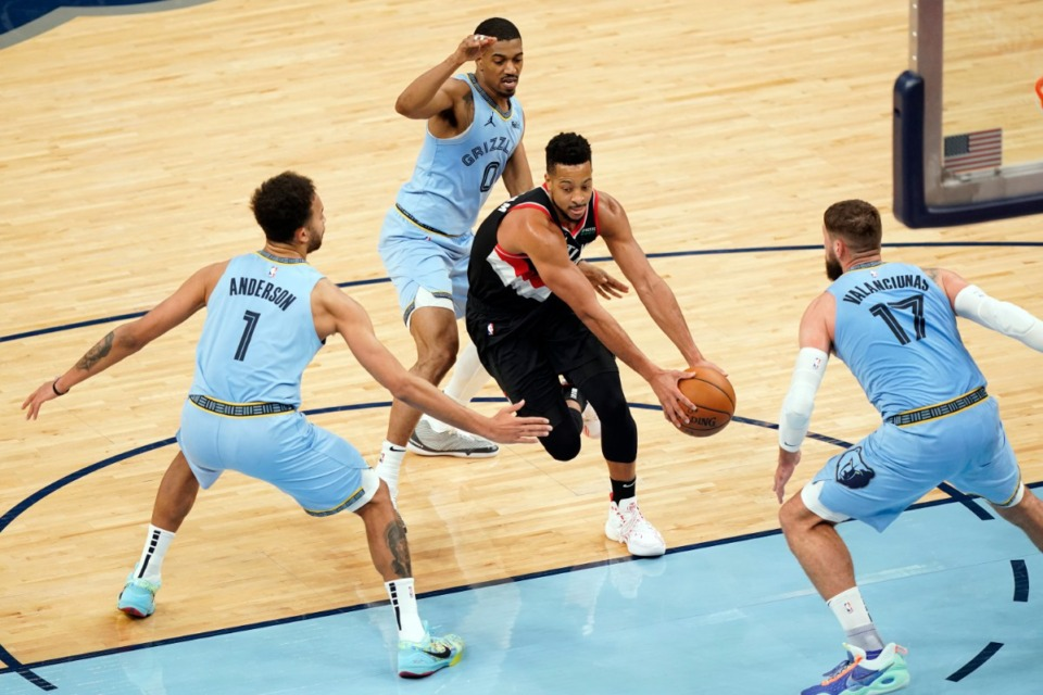 <strong>Portland Trail Blazers' C.J. McCollum, center, drives between Memphis Grizzlies' defenders Kyle Anderson (1), De'Anthony Melton (0) and Jonas Valanciunas (17) in the second half of an NBA basketball game Wednesday, April 28, 2021, at FedExForum.</strong> (Mark Humphrey/AP)