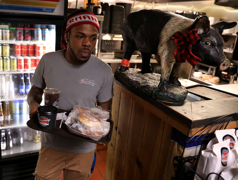 <strong>Madracus Davis, an eight-year employee of Germantown Commissary, carries out a to-go order to be bagged up Tuesday, Jan. 22, 2019. The restaurant's much-anticipated sister store, Collierville Commissary, is expected to open in mid-February.</strong> (Patrick Lantrip/Daily Memphian)