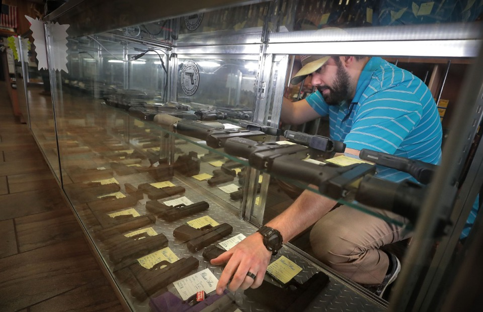 <strong>In just a few months, adults will be able to carry a handgun without a permit in Tennessee. Assistant manager Chris Richardson (in a 2020 file photo) arranges merchandise at the Classic Arms of Memphis gun store in Cordova. </strong>(Daily Memphian)