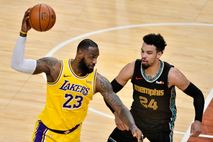 Los Angeles Lakers forward LeBron James (23) handles the ball against Memphis Grizzlies guard Dillon Brooks (24) in the second half of an NBA basketball game Tuesday, Jan. 5, 2021, in Memphis, Tennessee. (AP Photo/Brandon Dill)