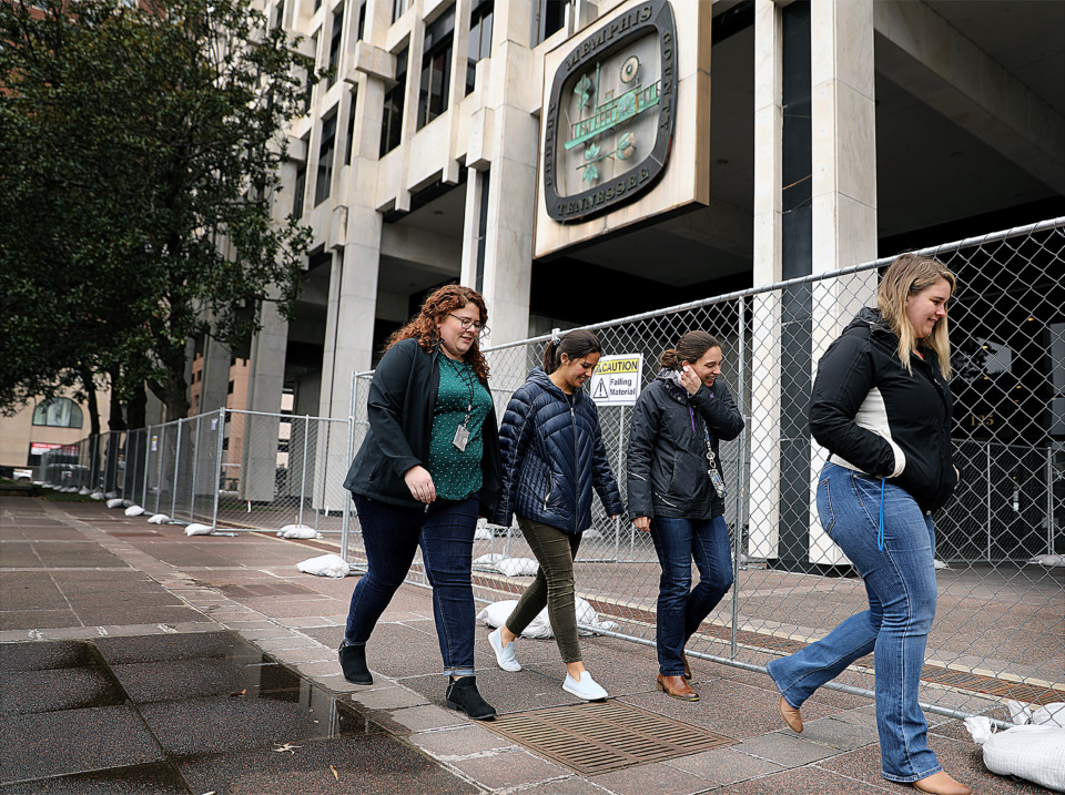 <strong>Alison Archibal, Holly Enlow, Sarah Girdner and Ashely Evans walk past Memphis City Hall Friday, Jan. 18, on their way back from lunch. The city has had to install fencing around the fa&ccedil;ade to protect passers-by from falling material.</strong> (Patrick Lantrip/Daily Memphian)