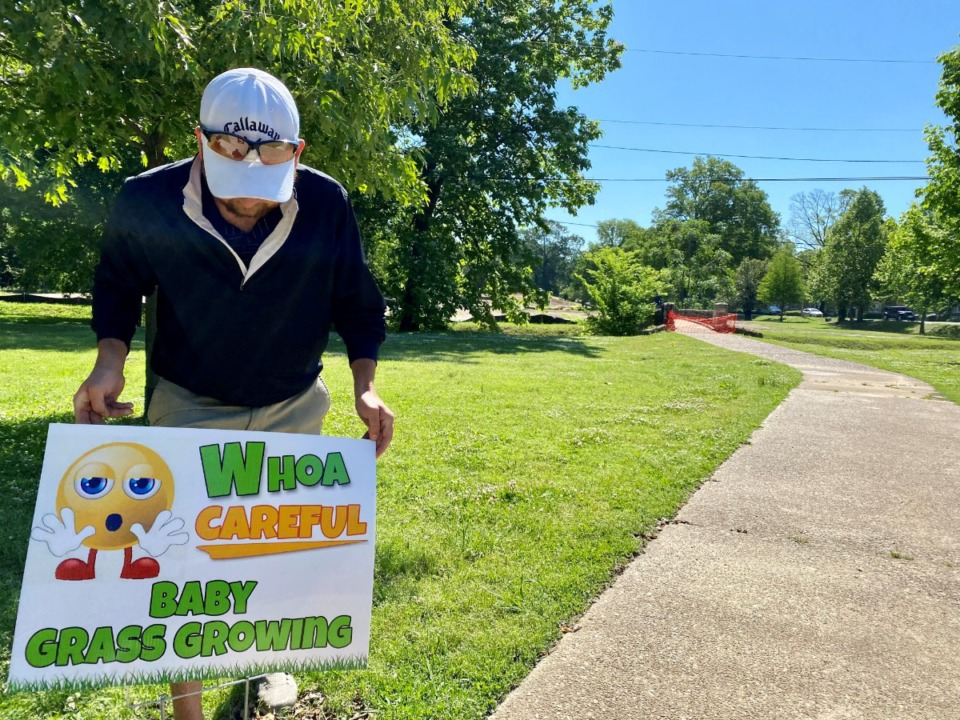 <strong>Patrick Canale, Overton Park golf course facilities manager, posts one of the new signs on Friday, May 7. The signs take a warmer approach than&nbsp;&ldquo;Stay off the grass.&rdquo;</strong> (Tom Bailey/Daily Memphian)