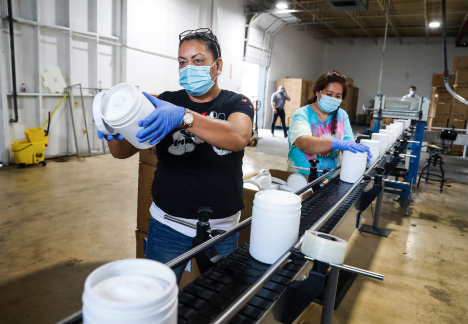 <strong>Pristex product workers Rosalba Herrera (left) and Alicia Hernandez place lids on disinfectant wipes on Monday, May 3, 2021. Pristex has partnered with MMDC and TNEX to provide PPE to Memphis-area hospitals.</strong> (Mark Weber/The Daily Memphian)