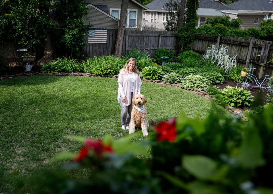 <strong>The backyard garden of Angie Wallick (shown with dog Wally) will be featured in this year&rsquo;s Cooper-Young Garden Walk on May 15-16. The walk will feature 90 gardens, including several hidden gardens.</strong> (Mark Weber/Daily Memphian)