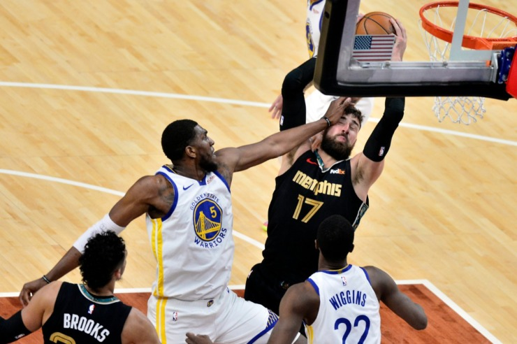 Memphis Grizzlies center Jonas Valanciunas grabs a rebound as he collides with Golden State Warriors center Kevon Looney in a March NBA game. (AP Photo/Brandon Dill)