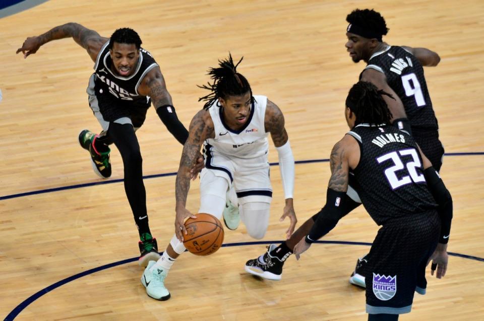 <strong>Memphis Grizzlies guard Ja Morant handles the ball between Sacramento Kings guard Delon Wright (55), center Richaun Holmes (22), and guard Terence Davis (9) in the first half of an NBA basketball game Thursday, May 13, 2021, at FedExForum.</strong> (Brandon Dill/AP)