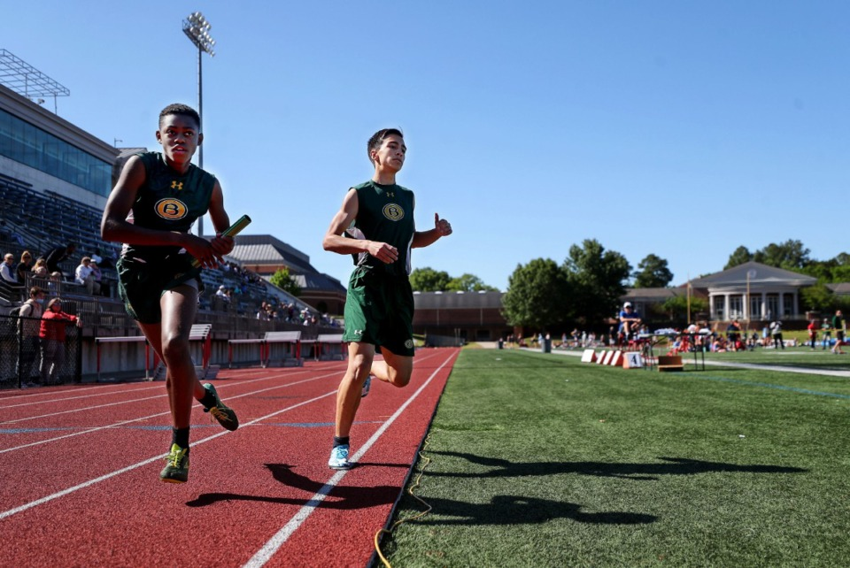 <strong>Briarcrest's Alex Barrios (right) hands off the baton to Camren Armstrong during the 4x800 meter relay at Memphis University School May 13, 2021.</strong> (Patrick Lantrip/Daily Memphian)