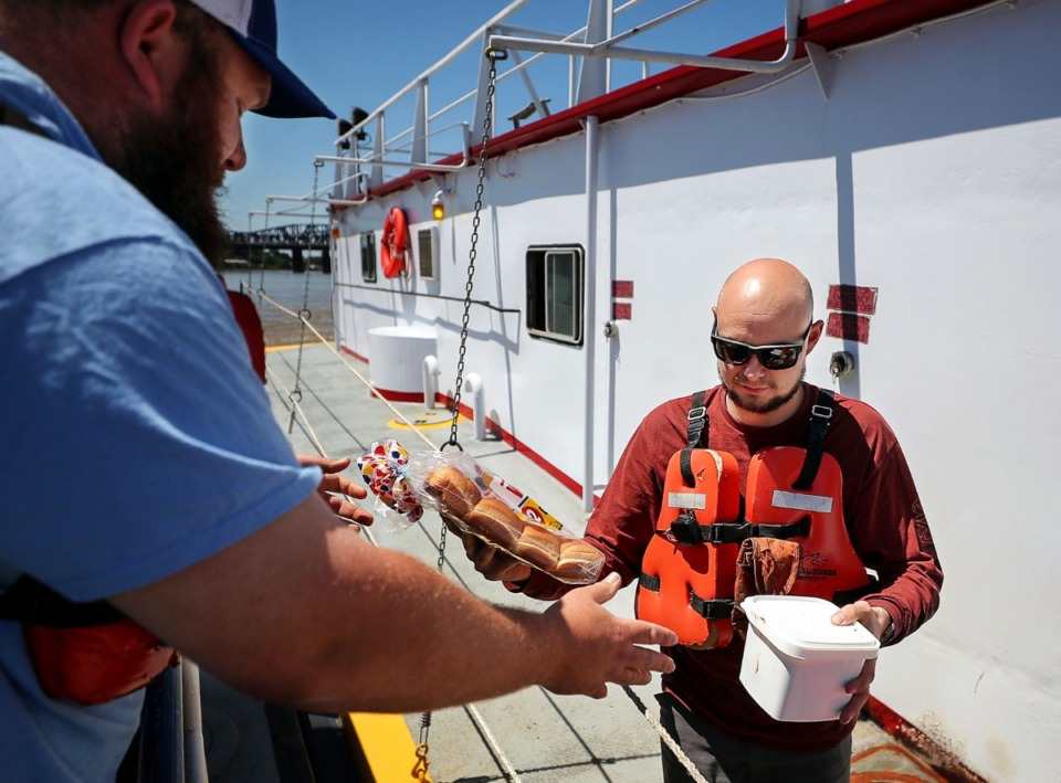 <strong>Brandon Massey (left) delivers an order of Rendezvous barbecue ribs, courtesy of Economy Boat Store, to Shaun Burtschi, who had been stuck on a barge while engineers assessed the safety of the Hernando DeSoto Bridge.</strong> (Patrick Lantrip/Daily Memphian)