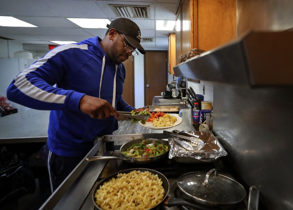 <strong>Kenny Henry prepares lunch for his crewmates who are awaiting permission to travel under the Hernando DeSoto Bridge on Friday, May 14.</strong> (Patrick Lantrip/Daily Memphian)