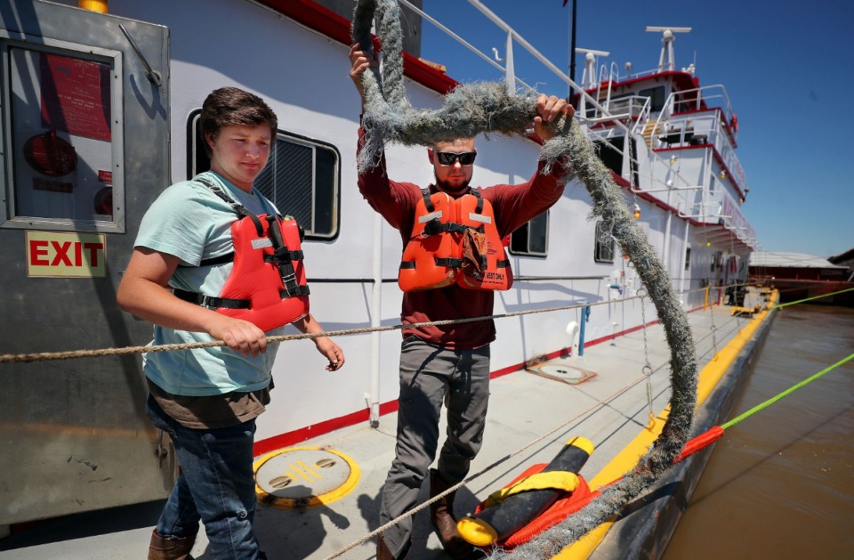 <strong>Shaun Burtschi (right) and Skyler Fowlkes unanchor a boat from their barge that delivered free barbecue to them while they were stranded on the Mississippi River</strong>. (Patrick Lantrip/Daily Memphian)