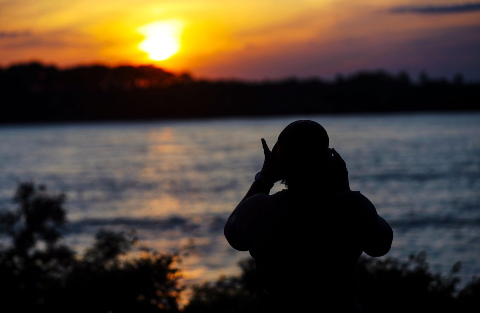 <strong>Sasha Taylor takes a picture of the sunset over the Mississippi River.</strong> (Patrick Lantrip/Daily Memphian)