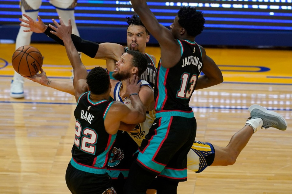 <strong>Golden State Warriors guard Stephen Curry, middle, is fouled while shooting between Memphis Grizzlies guard Desmond Bane (22), forward Jaren Jackson Jr. (13) and forward Dillon Brooks during the second half of an NBA basketball game in San Francisco, Sunday, May 16, 2021.</strong> (Jeff Chiu/AP)