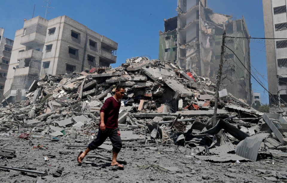 <strong>A man walks past the the rubble of the Yazegi residential building that was destroyed by an Israeli airstrike, in Gaza City, Sunday, May 16, 2021. The 57-member Organization of Islamic Cooperation held an emergency virtual meeting Sunday over the situation in Gaza calling for an end to Israel&rsquo;s military attacks on the Gaza Strip.</strong> (Adel Hana/AP)