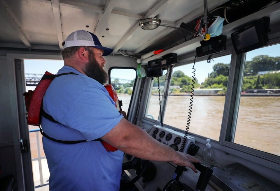<strong>Brandon Massey drives a boat carrying Rendezvous barbecue to a barge waiting for permission to travel under the Hernando Desoto Bridge on Friday, May 14.</strong> (Patrick Lantrip/Daily Memphian)
