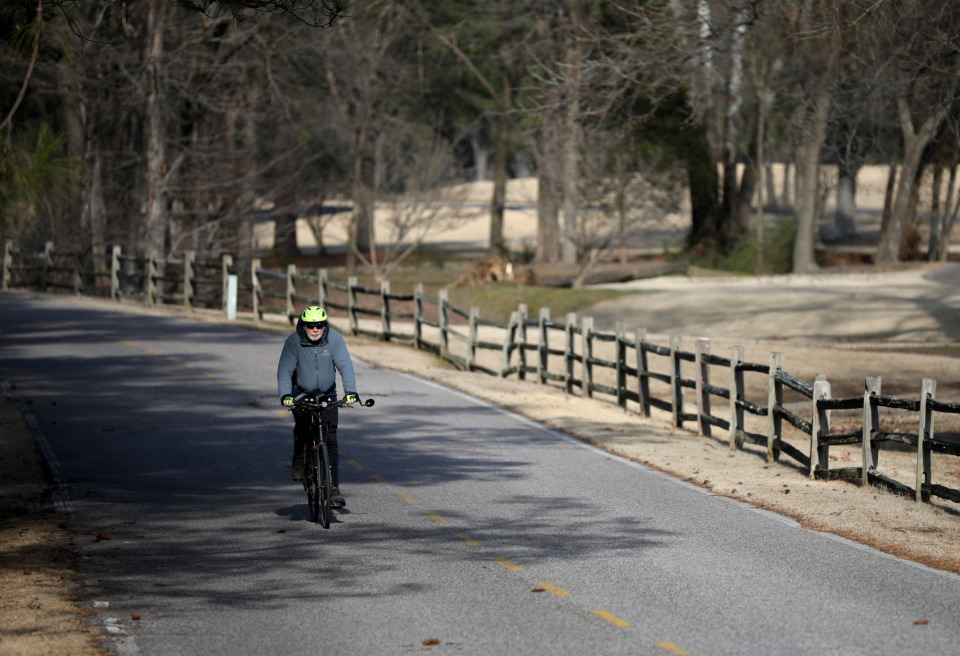 <strong>A cyclist cruises down the entry drive to Germantown Country Club during his routine 10 mile route. Residents of the neighborhoods surrounding the golf course frequently bike or walk through the courses golf cart paths.</strong> (Houston Cofield/Daily Memphian)